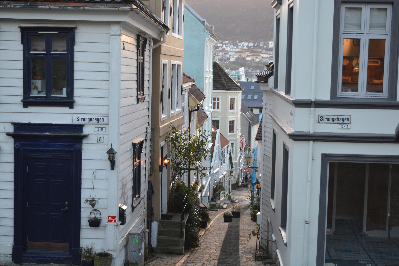 Une ruelle typiquement bergenoise, dallée et entourée de petites maisons en bois blanc.