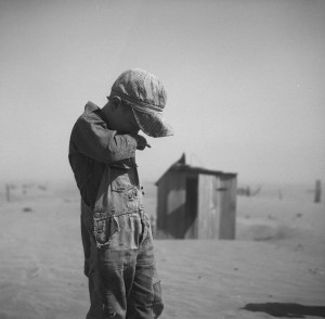 A young boy covers his mouth during a dust storm on farm. Cimarron County, Oklahoma. April 1936.
