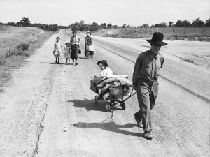 Migrant family walking on road, pulling belongings in carts and wagons. Pittsburg County, Oklahoma. June 1938.